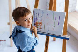 Close-up portrait of cute, smiling, white three years old boy in blue shirt and jeans apron with brush in the hand. Concept of early childhood education, painting, talent, happy family or parenting