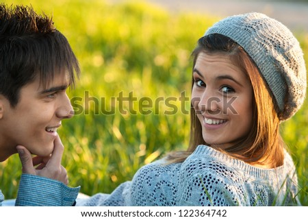 Close up portrait of cute teen girl and boyfriend laying in green grass field.