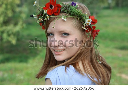 Close up portrait of Cute teen girl with a wreath of spring flowers on sunny day