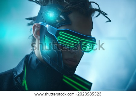 Close up portrait of cyberpunk warrior of the future in green virtual reality glasses on blue digital background. Game, virtual reality. Future technologies.