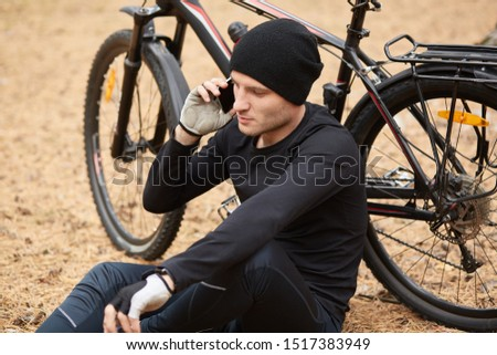 Close up portrait of cyclist resting in open air, sitting on ground in field or forest and talking on phone, wears sport wear and cap, having serious conversation with friend or wife while rides bike.