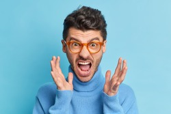 Close up portrait of displeased young man raises hands and screams loudly being annoyed with something keeps mouth widely opened wears optical glasses and turtleneck poses indoor. People irritation
