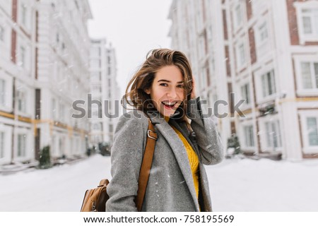 Close-up portrait of ecstatic woman in elegant gray coat standing on the street in snowy day. Outdoor photo of fashionable female model with brown bag walking around city in winter vacation.