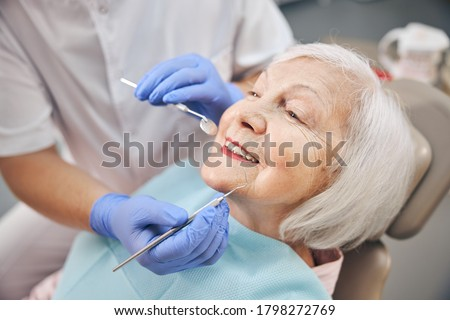 Close up portrait of elderly beautiful woman check up and having the consultation with dentist at the dental office Stock photo ©