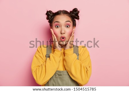 Close up portrait of emotive Asian girl, touches cheeks, stares with eyes popped out, holds breath from excitement, wears yellow sweatshirt and overalls, isolated over pink background. Omg concept