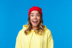 Close-up portrait of excited and intrigued young hipster girl in red beanie and yellow hoodie, gasping amazed look camera wondered and entertained, standing blue background