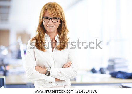 Close-up portrait of executive business woman standing at office. Business people.