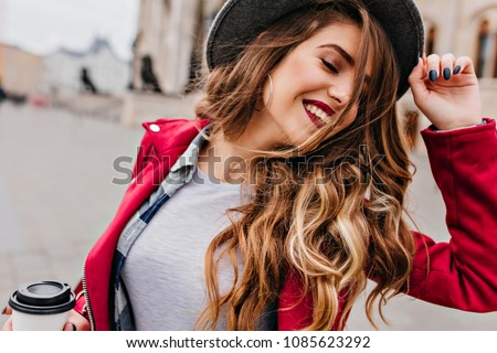 Close-up portrait of fascinating white woman with golden wavy hair posing with eyes closed on the street. Romantic relaxed girl in hat holding cup of latte.