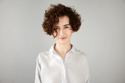 Close up portrait of fashionable hipster female with short curly hairstyle wearing white trendy shirt, having fun, looking at the camera with mysterious smile. Human face expressions and emotions