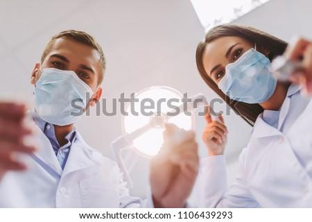 Portrait of female dentist holding dental tools in dental