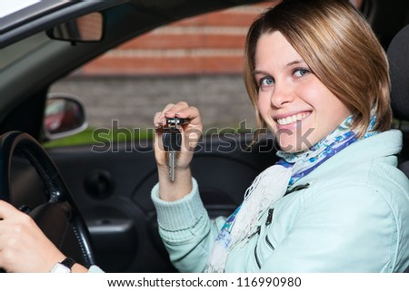 Close up portrait of female driver with car key in hand