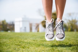 Close-up portrait of female legs jumping on the grass outdoors in the park