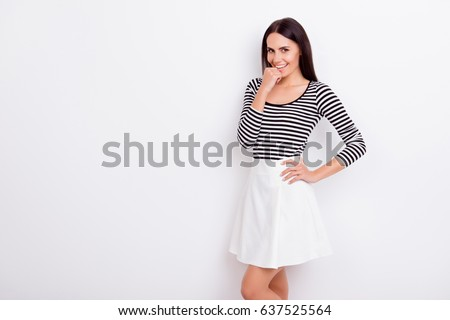 Close up portrait of flirty attractive lady. She is wearing casual outfit and stands on pure white background