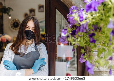 Close up portrait of floral shop woman owner in gloves with face mask, open door after lockdown quarantine. Announcement we are open nv doors, flower shops, cafes, local, small businesses concept.
