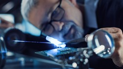 Close-up Portrait of Focused Middle Aged Engineer in Glasses Working with High Precision Laser Equipment, Using Lenses and Optics for Accuracy Electronics. Testing Superconductor Material