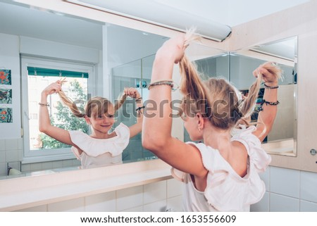 close up portrait of funny beautiful girl with braid hairdo laughing while looking into bathroom mirror