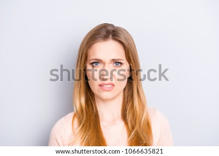 Close up portrait of funny confused puzzled unhappy upset sad uncertain unsure beautiful pretty charming grimacing woman with long blonde hairdo isolated on gray background opy-space #1066635821