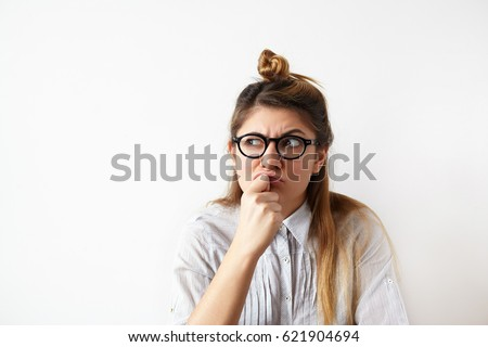 Close up portrait of funny confused woman in glasses thinking and looking aside standing on white wall background. Copy space on the side. Human expressions, emotions, feelings, body language