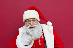 Close up portrait of funny happy excited old bearded Santa Claus face wearing hat, glasses, looking at camera, showing pointing finger gesture choosing you for advertising isolated on red background.