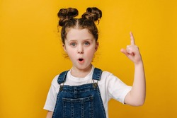 Close up portrait of funny little girl make gesture raises finger came up with creative plan feels excited with good idea, inspiration motivation, isolated on yellow wall, brain work eureka concept