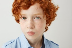 Close up portrait of funny little kid with orange hair and freckles. Boy looking in camera with relaxed and calm face expression.
