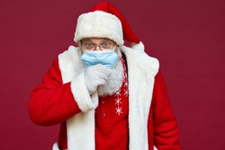Close up portrait of funny old bearded sick ill Santa Claus wearing costume, glasses, face mask coughing looking at camera standing on Christmas red background. Covid 19 coronavirus concept.