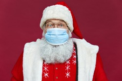 Close up portrait of funny old bearded surprised Santa Claus wearing costume, glasses, face mask looking at camera standing on Christmas red background. Covid 19 coronavirus safety protection concept.