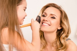 Close up portrait of girl doing makeup to her cheerful mom
