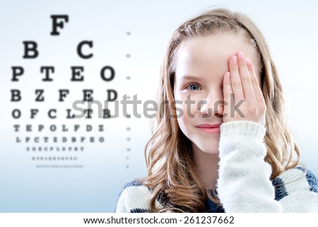 Close up portrait of girl reviewing eyesight closing eye with hand.Out of focus test chart in background. #261237662