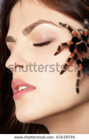 close-up portrait of girl with brachypelma smithi spider creeping over her face