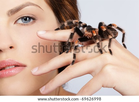 close-up portrait of girl with brachypelma smithi spider sitting on her hand