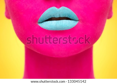 Close-up portrait of girl with pink skin and blue lips on yellow - stock photo