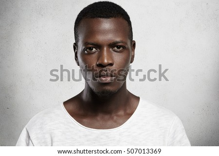 Close up portrait of good-looking serious African man with healthy clean skin wearing white casual t-shirt posing isolated against gray studio wall with copy space for your promotional content #507013369