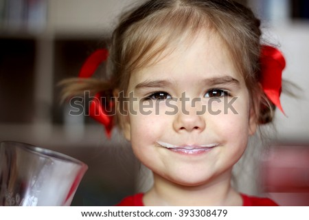Close-up portrait of gorgeous little girl with milk mustache drinking a glass of milk at home, food and drink concept, healthy food, indoor