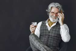 Close up portrait of grinning old-fashioned man. Elegant man in a studio. Grandfather with a cigar and whiskey.