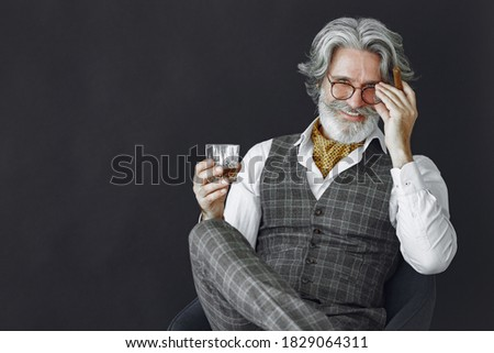 Close up portrait of grinning old-fashioned man. Elegant man in a studio. Grandfather with a cigar and whiskey. Stock photo ©