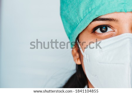 Close up portrait of half face of  young Indian female surgeon doctor in Emergency room wearing mask and cap during corona virus pandemic Foto stock ©