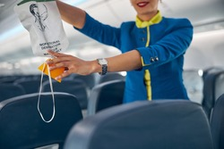 Close up portrait of hands of flight attendant on a commercial passenger jet reaching for an oxygen mask