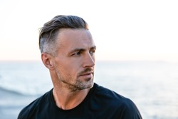 close-up portrait of handsome adult man with grey hair looking away on seashore