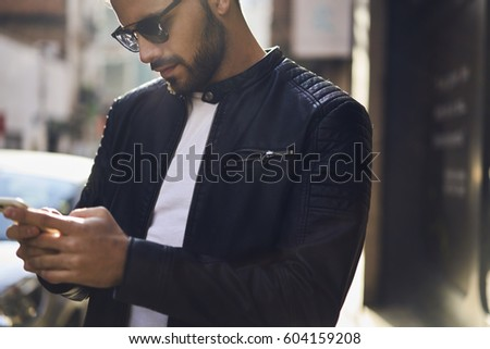 Close up portrait of handsome confident man dressed in trendy leather jacket going to cafe for meeting with best friends in evening texting feedback in social networks comment followers requests  #604159208