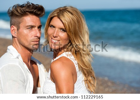 Close up portrait of handsome couple in white on beach.