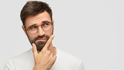 Close up portrait of handsome dark haired male holds chin and looks with hesitsation aside, chooses what to buy between two things, isolaed over white background with copy space for your text