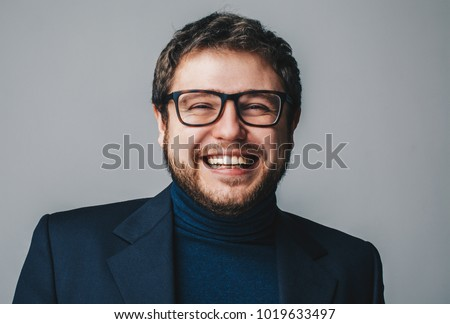 Close up portrait of handsome happy young business man smiling with white teeth isolated on grey background.