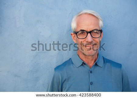 Close up portrait of handsome senior man with glasses looking at camera, he is standing against a blue wall. #423588400