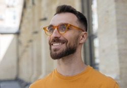Close up portrait of handsome smiling bearded man wearing stylish eyeglasses looking away on the street