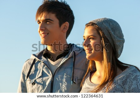Close up portrait of handsome teen couple looking in the distance outdoors.