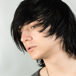 Close-up portrait of handsome teenage boy with black hair emo hairstyle on white background.
