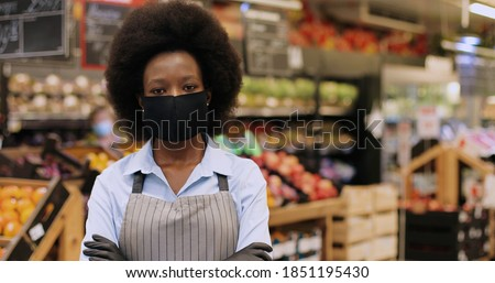 Close up portrait of happy African American female Worker in black mask and gloves standing in supermarket and looking at camera. Young woman food store assistant at work in quarantine Imagine de stoc ©