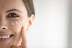 Close up portrait of happy beautiful millennial Caucasian female apply nourishing under-eye cream against wrinkles. Smiling young woman use moisturizing balm on face skin. Skincare concept.