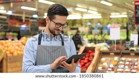 Close up portrait of happy Caucasian male worker in glasses standing in supermarket and typing on tablet. Young joyful man food store assistant at work tapping on device indoors. Retail concept Imagine de stoc ©